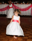 Flower girl twirls her dress at reception